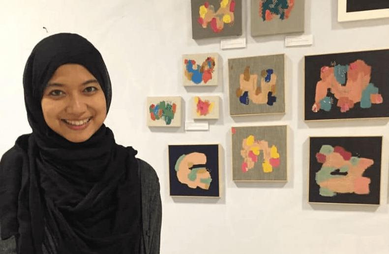 Kunstenaar Nadia Nizamudin met op de achtergrond haar werken