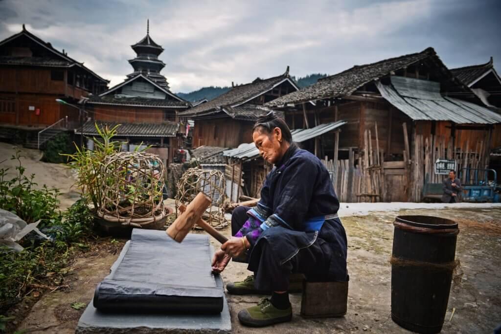 Een Dong vrouw kalandeert een doek, die eerst met indigo is geverfd, Si Zhai, Liping, (foto: Wu Zeng Ou).